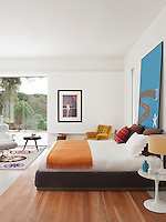 A contemporary, white bedroom with full height windows. A white leather Eames recliner stands on a vibrant carpet entitled Stela by Carpet Diem. A Hermes orange blanket is draped at the foot of the double bed. A retro lamp sits on an Eero Saarinen Tulip table.