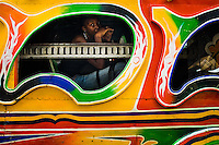 A Haitian girl looks out of the window of the tap-tap bus in Delmas, Port-au-Prince, Haiti, 24 July 2008. Tap-tap vehicles serve as public transportation in Haiti. They are private, operate over fixed routes, departing only when full. Tap-taps are decorated with bright and shiny colors and with a lot of fancy designed elements. There are scenes from the Bible, Christian slogans, TV stars or famous football players often painted on a tap-tap body. Tap-tap name comes from sound of taps on the metal bus body signifying a passenger's request to be dropped off.