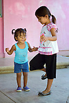 In Zapotal, Mexico, 3-year old Luz Elena Martinez (left) goes to preschool one hour a day to help prepare her to go full time the following year. In this image, the girl, who is blind, is holding hands with her older sister, 5-year old Sandra, during a game. Sandra will graduate from preschool the coming year, but before that she's getting Luz accustomed to the school environment to make for an easier transition.