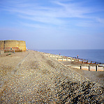 Martello tower and wooden groynes on shingle beach, Slaughden, Aldeburgh, Suffolk, England