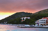 View of the harbour jetty in Brna village and the Danny hotel and restaurant at sunset with an overcast orange sky. Prizba village. Korcula Island. Prizba, Riva Apartments, Danny Franulovic. Korcula Island. Dalmatian Coast, Croatia, Europe.