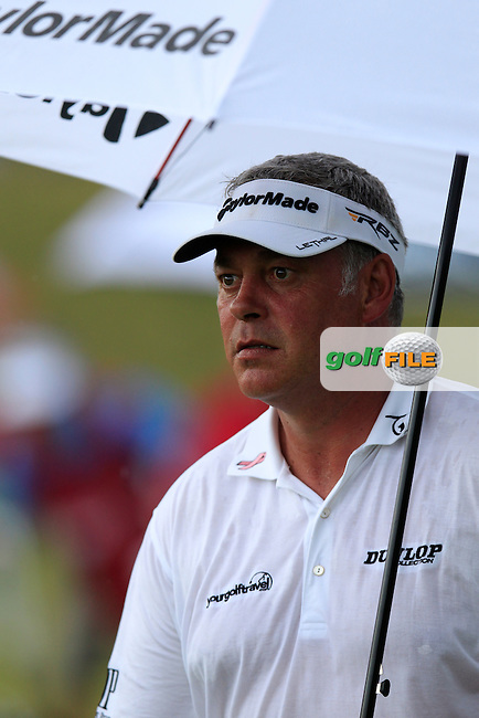 Darren Clarke (NIR) takes shelter as he walks to the 9th tee during Thursday's Round 1 of the 113th U.S.Open National Championship held at Merion Golf Club, Ardmore, Philadelphia, Pennsylvania. <br /> 13th June 2013<br /> (Picture: Eoin Clarke www.golffile.ie)