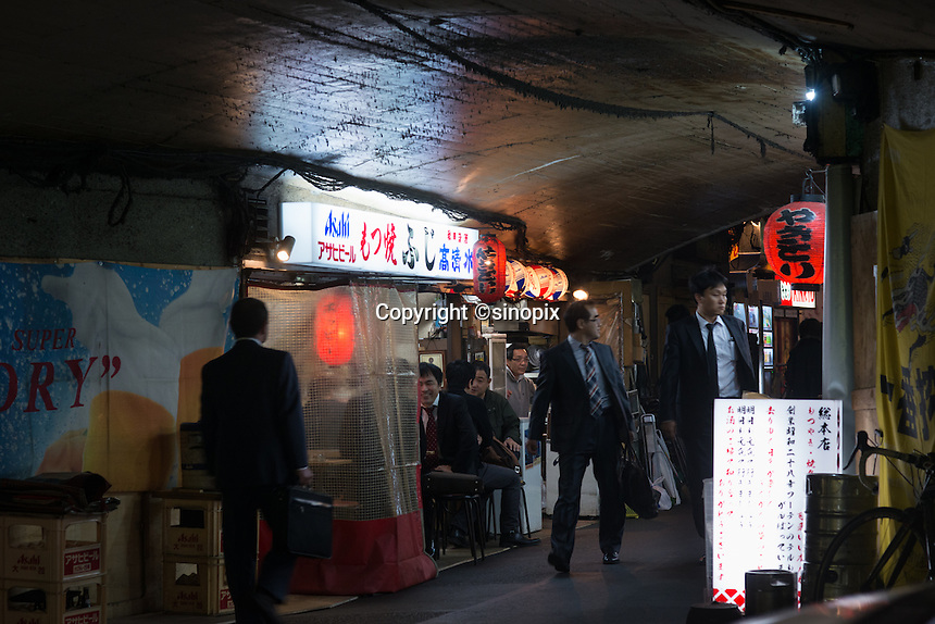 Salaryman enjoy drinking at the Yakitori bars under the railway track  at Shinbashi station