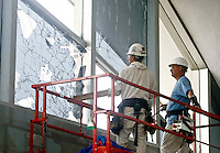 Tommy Holland (L) and Scott Keller (R), of Bam Contracting,  work on windows in the main terminal of Lambert- St. Louis International Airport on April 23, 2011 after storms last night damaged both the interior and exterior of the airport. The airport was closed all day today and officials hope to reopen tomorrow. REUTERS/Sarah Conard (UNITED STATES)
