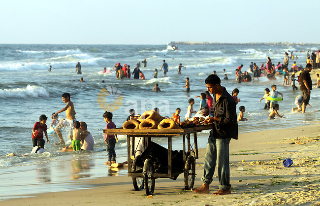 A Palestinian man sells bread as others enjoy swimming in the sea on Gaza's beach on 27 June 2012 in Gaza . Photo by Majdi Fathi