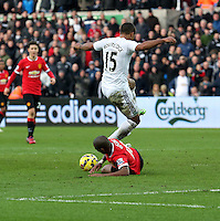 SWANSEA, WALES - FEBRUARY 21: Wayne Routledge of Swansea jumps over Ashley Young of Manchester during the Barclays Premier League match between Swansea City and Manchester United at Liberty Stadium on February 21, 2015 in Swansea, Wales.