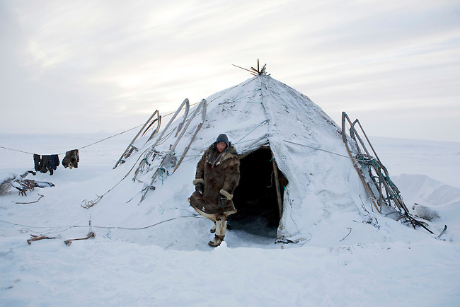 Vitya Nutetgevev, a young Chukchi reindeer herder stands in the doorway of a Yaranga (traditional tent). Chukotskiy Peninsula, Chukotka, Siberia, Russia
