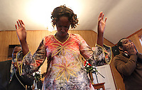 Esperance Nyabanama, middle, feels the music as she sings alongside Pastor Peter Chege, left, and Derrick Muchembe, right, during Sunday service at The Africa Lighthouse Baptist Temple near Stony Point in Albemarle County, VA. The small 10 family congregation is made up of African refugees and immigrants who's service is spoken in Swahili and translated into English. They've just signed a rent-own lease for a small church after meeting for three years at a local school. Photo/The Daily Progress/Andrew Shurtleff
