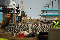 Workers repair a boardwalk while a crane works to remove remnants of the Jet Star roller coaster that had been left in the ocean after Superstorm Sandy hit Seaside Heights last year, in New Jersey  May 14, 2013, Photo by Eduardo Munoz Alvarez / VIEWpress.