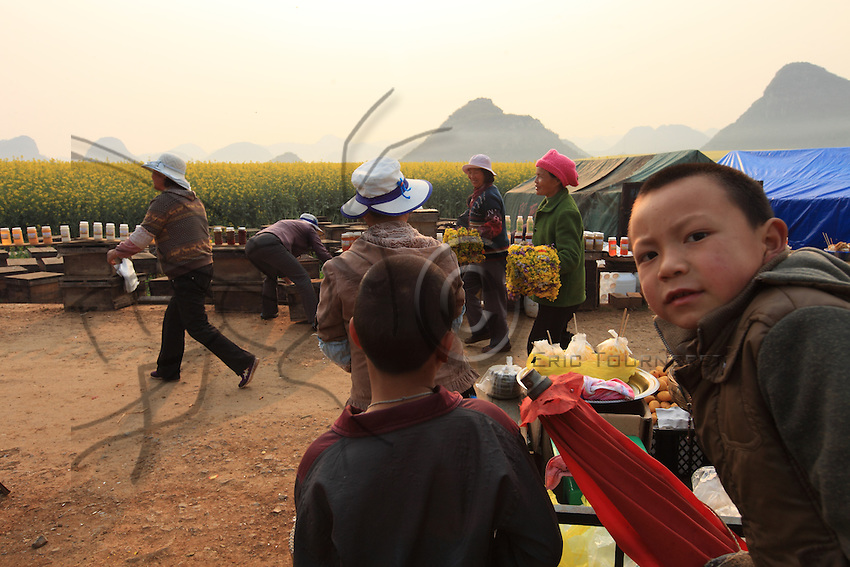 Luoping, Yunnan. The road that leads to the hills has become an open-air market. Beekeepers and other vendors await the tourists.