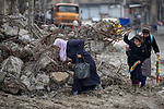 A woman and two girls navigate amid the mud and rubble of the Old City of Mosul, Iraq, which was devastated during the 2017 Battle of Mosul, which led to the defeat of the Islamic State group, also known as ISIS.