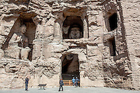 Visitors admiring large Buddha statues at the Yungan Grottoes in Datong, China
