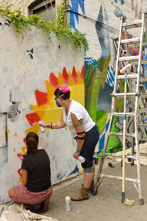 The women collaborate on a mural.
