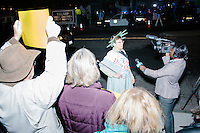A reporter interviews a woman dressed as the Statue of Liberty in front of anti-Trump protesters gather near the Sheraton Portsmouth Harborside Hotel in Portsmouth, New Hampshire, USA. At the hotel later that evening, Republican presidential candidate and real estate mogul Donald Trump received an endorsement from the New England Police Benevolent Association executive council. Many protesters expressed disagreement with Trump's recent statements that he would ban all Muslims from entering the country. Trump brought up the recent shooting in San Berdardino, Calif., at the meeting. A small group of perhaps 20 Trump supporters stood outside the hotel. One of the protest organizers estimated that there were around 230 protesters gathered.