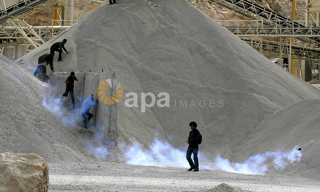 Palestinian demonstrators take cover during a protest against Israel's separation barrier in the West Bank village of Shuqba, near Ramallah, Friday, Dec. 11, 2009. Israel says the barrier is necessary for security while Palestinians call it a land grab. Photo by Issam Rimawi