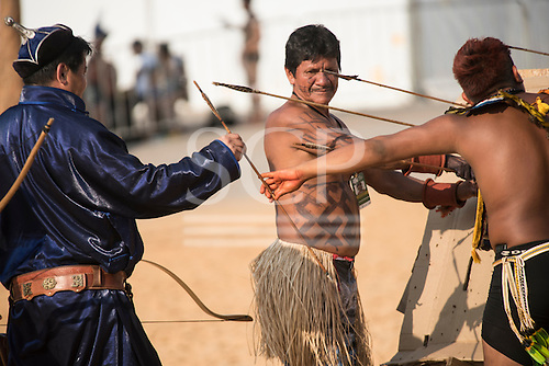A Brazilian and a Mongolian archer exchange arrows while the oldest contestant, from the Mamandé tribe, looks on during practice at the International Indigenous Games, in the city of Palmas, Tocantins State, Brazil. Photo © Sue Cunningham, pictures@scphotographic.com 28th October 2015