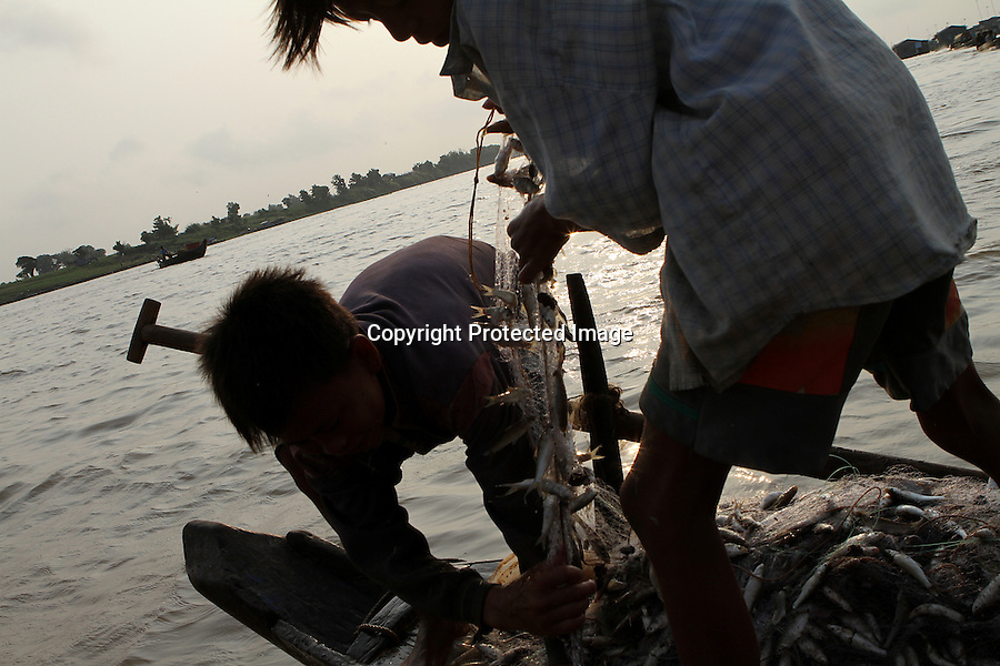 Two young fishermen are lifting a net on the Tonle Sap river at Kompong Chhnang, Cambodia-2011