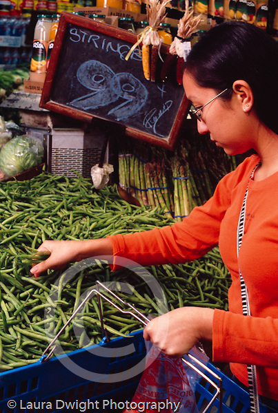 College student female shopping for vegetables: green beans at produce display