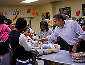 United States President Barack Obama plays with the young child of a customer as he packs and gives bags of food to area residents, with the help of his daughter Sasha, center, at Martha's Table on Wednesday, November 24, 2010, in Washington, DC. .Credit: Leslie E. Kossoff - Pool via CNP