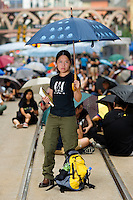 HONG KONG, HONG KONG SAR, CHINA - OCTOBER 04: Mandy Li, 34, poses for a photograph holding a symbolic umbrella as she and other protesters occupy Yee Wo Street, part of pro-democracy 'Occupy Central' camp in Causeway Bay, Hong Kong, on October 4, 2014. Mandy Li, a commerce analyst, says: 'These last 17 years (since the handover of Hong Kong to the People's Republic of China) we trusted politicians to obtain universal suffrage. That failed, and we realized that unless we take things in our own hands, there won't be any progress'. The 'Umbrella revolution' or 'Occupy Central' is a civil disobedience movement that began in response to China's decision to allow only Beijing-vetted candidates to stand in the city's 2017 election for the top civil position of chief executive. Thousands of pro-democracy supporters are calling for open elections and the resignation of Hong Kong's Chief Executive Leung Chun-ying. (Photo by Lucas Schifres/Getty Images)