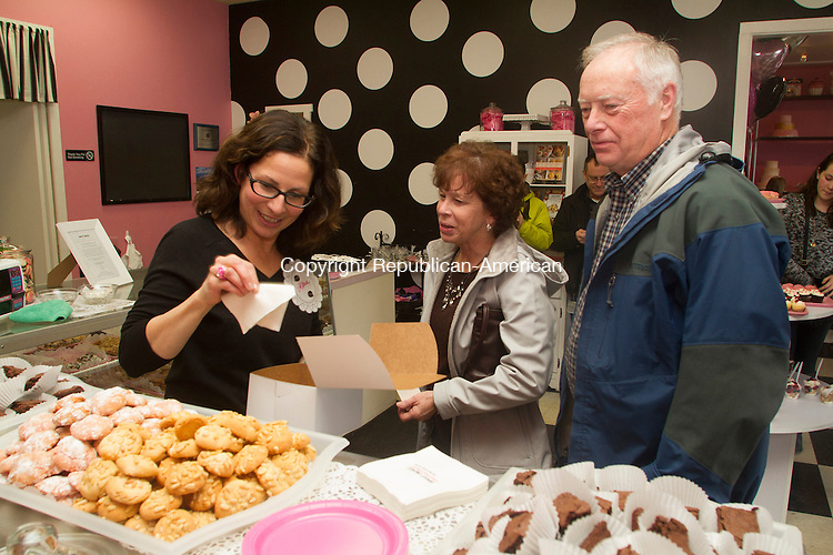 WATERBURY, CT.- 08 MARCH 2015 - 030815JW07 - Sweet Maria's owner Maria Sanchez helps customers Donna Marconi and John Martin  her bakery's 25th anniversary in which she donated 25 birthday cakes to children who are patients at Connecticut Children's Medical Center's unit at Saint Mary's Hospital in Waterbury Sunday afternoon.<br /> Jonathan Wilcox Republican-American