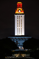 UT Tower at night after a football win where the top of the tower is burnt orange.  The UT Tower is located in the center of University of Texas campus it is 307 feet tall with 30 floors so it is part of the cityscape and can be seen from most place on or near the campus which is located in downtown Austin. This is part of Austin cityscape and it a Texas landmark in the city this version is a vertical or tall capture of the Tower.
