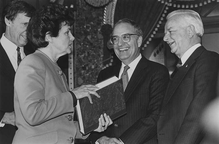 Richard C. Blum (husband of Sen. Dianne Feinstein), Sen. Dianne Feinstein, D-Calif. is holding Byrd's History of Senate book, given to her by Sen. Robert Byrd, D-W.Va. She is chatting with Sen. George Mitchell, D-Maine, on Nov. 12, 1992. (Photo by Laura Patterson/CQ Roll Call via Getty Images)