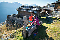 Filling water bottles at a fountain and getting ready at the Cabane d'Essertze for day 2 of the Via Valais, a multi-day trail running tour connecting Verbier with Zermatt, Switzerland.