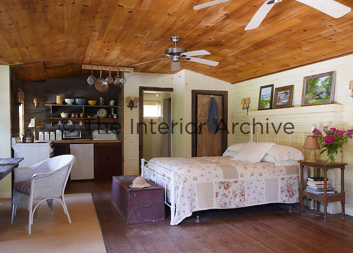 A bedroom in the guest cottage is furnished with its own small kitchen