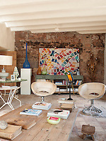 A large photograph of colourful paint swatches is the focal point of one end wall of the living room which has been left with the original bricks exposed