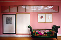 A 19th century daybed stands against the pink walls of the dining room decorated with contemporary artworks by Fabrice Hybert