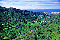 Sweeping aerial shot of Nuuanu Valley on Oahu showing the lush green Koolau mountain ridge  with downtown Honolulu and the beautiful blue Pacific Ocean in the distance.