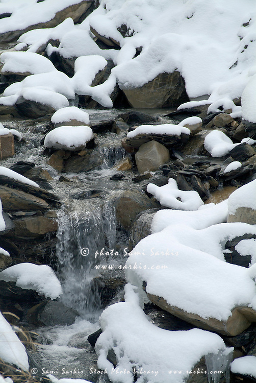 Snow-covered rocks beside a mountain stream in the French Alps, France.