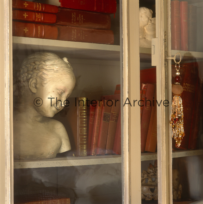 A charming bust of a young girl and books with red bindings are arranged in a display cabinet with glass doors.