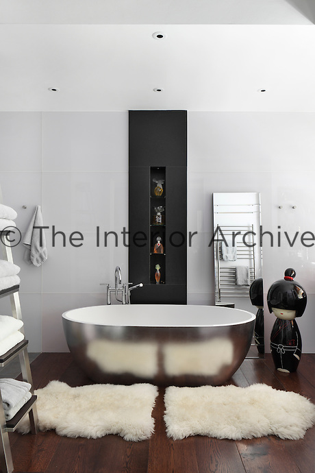 A luxury ensuite bathroom with a free-standing silver bath