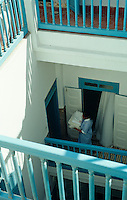 A chambermaid carrying fresh laundry between the bedrooms on the first floor landing