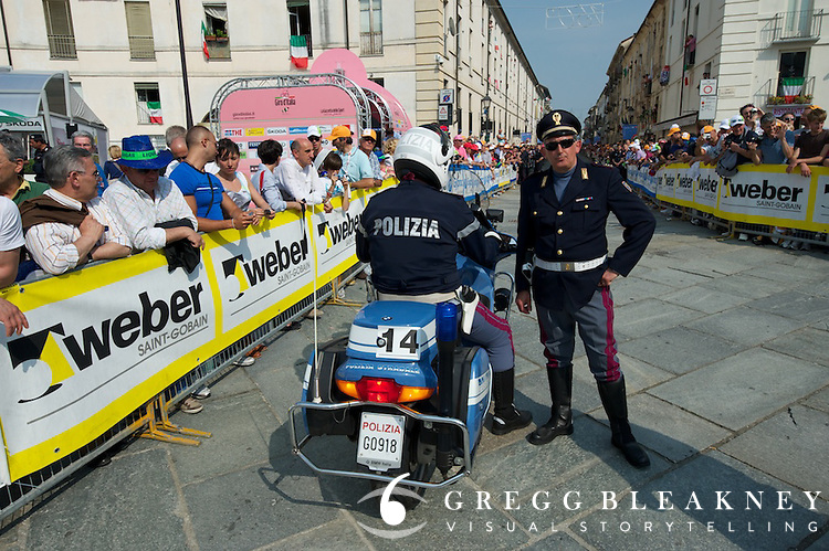 With massive starting line crowds, the Giro's police force has the tough job of keeping the course clear.