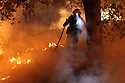 With firehose in hand, a fireman works to contain the 6,000 acre Border Fire in eastern San Diego County, California, USA, on Tuesday, June 21, 2016.