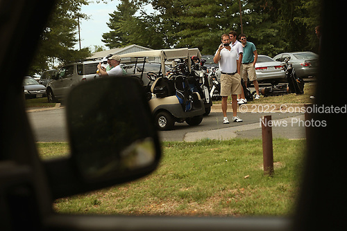 Golfers take photographs and videos of the motorcade carrying UNited States President Barack Obama to the golf course at Ft. Belvoir Army installation July 15, 2012 in Fort Belvoir, Virginia. Obama also campaigned in Virginia, a state he won in 2008, on Saturday, holding events in Fairfax and Glen Allen.  .Credit: Chip Somodevilla / Pool via CNP