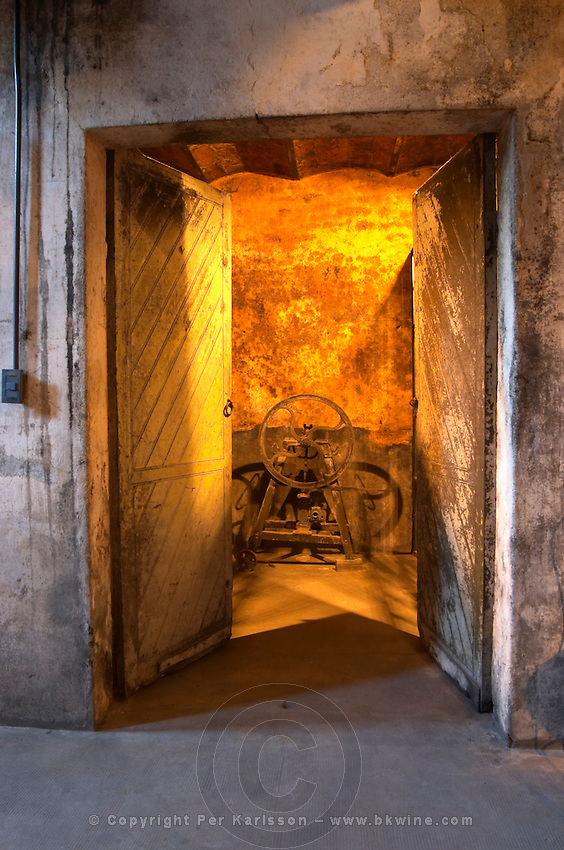 The entrance to the underground wine cellar, two large old wooden doors opening to a yellow light. Bodega Juanico Familia Deicas Winery, Juanico, Canelones, Uruguay, South America