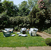 A group of painted wicker chairs and sofas in the spacious London garden