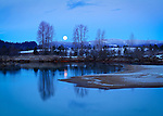 Idaho, North, Silver Valley, Cataldo. A full moon about to set before sunrise over the Coeur d'Alene River in winter.