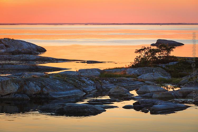 Spegelblankt vid Kallskär i ytterskärgården vid en gul solnedgång.