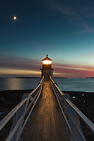 Marshall Point Lighthouse shines its beam into the evening sky to assist  mariners entering and leaving Port Clyde Harbor in Port Clyde, Maine.  The waxing crescent moon and the planet Venus (just to the right of the lighthouse) follow the sun into the western sky, still glowing red shortly after sunset.