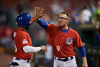 Buffalo Bisons Andy Burns (9) high fives Richard Urena (16) after scoring a run during an International League game against the Norfolk Tides on June 21, 2019 at Sahlen Field in Buffalo, New York.  Buffalo defeated Norfolk 1-0, the second game of a doubleheader.  (Mike Janes/Four Seam Images)