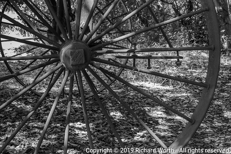 Close-up of the wheel on an antique farm implement displayed on the ground of Garin Regional Park in Hayward, California.