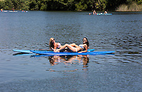 Young attractive, fit, sexy females sun tan on SUP stand up paddle board on Lady Bird Town Lake.