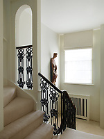 The staircase has a neutral stair carpet and wrought-iron spindles with a wooden banister.