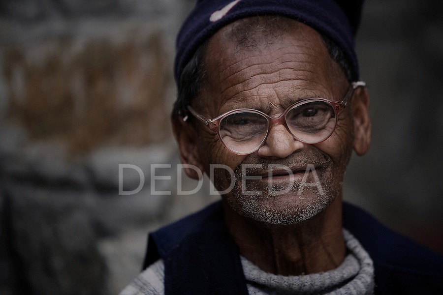 """An elderly gentleman wears a pair of glasses and a hat at an """"Aged Shelter"""" in Pokhara, Nepal."""