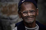 "An elderly gentleman wears a pair of glasses and a hat at an ""Aged Shelter"" in Pokhara, Nepal."